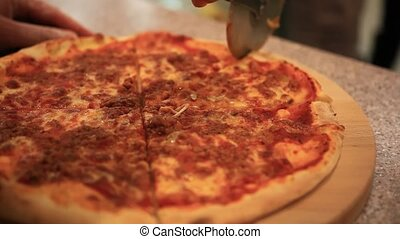 Cutting italian pizza with mushrooms, ham and cheese Close...