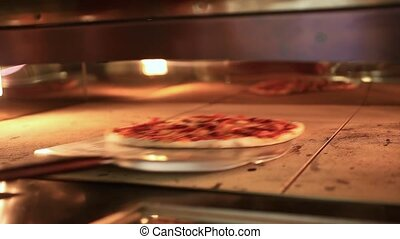 Ready pizza getting from oven and close Oven
