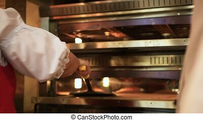 Chef puts dough in the oven for pizzas, traditional cooking