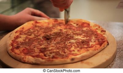 Cutting italian pizza with mushrooms, ham and cheese. Close...