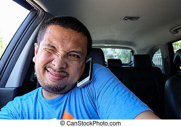 Asian man using phone while driving the car