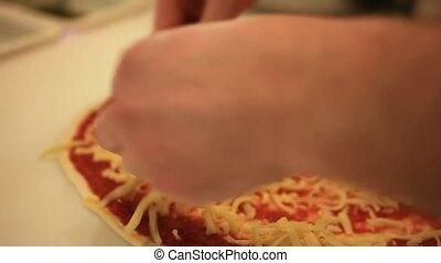 Hand chef puts cheeze on a pizza. Macro