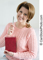 Positive woman with a notebook and pen in hand - Positive...