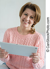 Positive woman with tablet computer in the hands