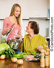 Happy mature woman with adult daughter cooking  together