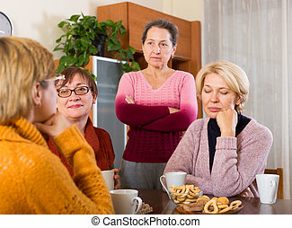 sad  female pensioners  sharing problems at table  indoor