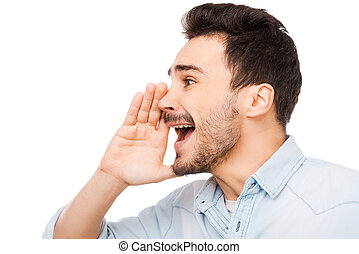 Great news! Cheerful young man holding hand near mouth and shouting while standing against white background