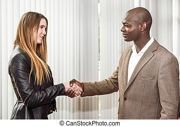 Black businessman shaking hands with a blonde caucasian woman