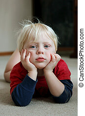 Adorable Young Child Laying on Living Room Floor - An...