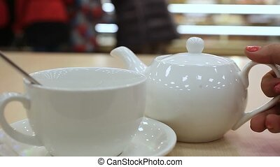 White Teapot pouring tea into a cup