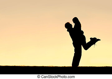 Silhouette of Happy Young Couple Hugging Outside at Sunset -...