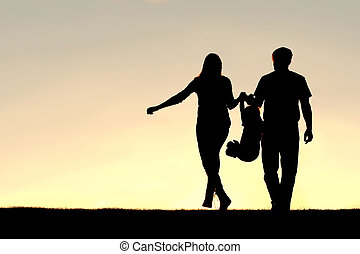 Silhouette of Family of Three People Walking at Sunset - A...