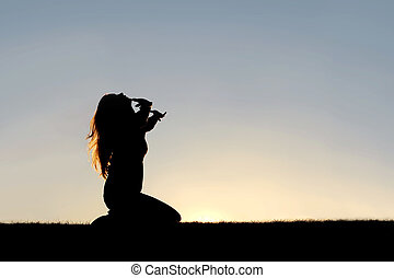 Silhouette of Woman Kneeling in Prayer and Surrender - A...