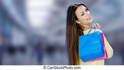 Happy female shopper carrying her purchases