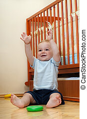 Hands up - Cute boy is sitting near his bed with hands up