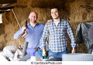 Two farm workers in hayloft - Two happy farm workers tedding...