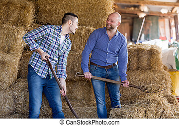 Two farm workers in hayloft - Adult smiling farm workers...