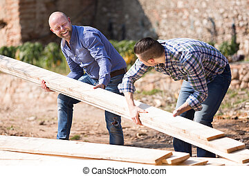 Farmers working with construction materials - Two happy...