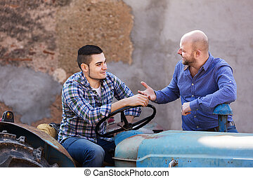 Farmers near agricultural machinery - Two happy farmers...