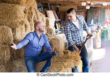 Two farm workers in hayloft - Two happy farm workers working...