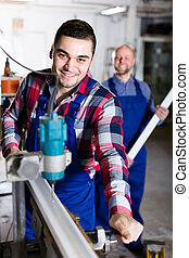 Two workmen in PVC shop - Two cheerful smiling men in...
