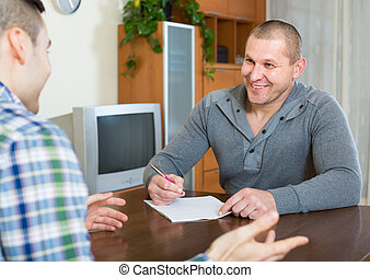Agent and client with documents at home - Male agent...