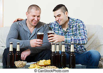 Two man with beer sit and talk - Young man drinks beer with...