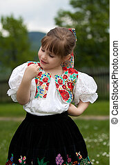 Small girl in traditional dress on the meadow - Little girl...