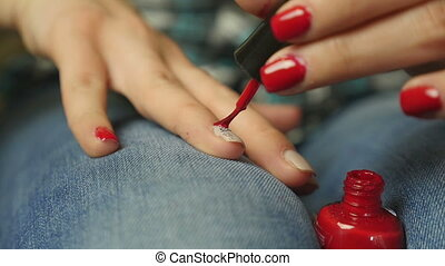 Young woman coloring her nails red - Young woman coloring...