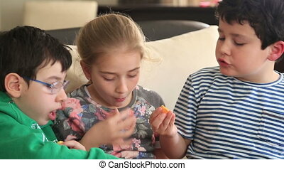 Friends eating potato chip - Three happy friends eating...