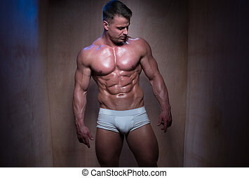 Muscular Man in White Boxer Shorts Looking Down - Muscular...