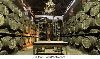 Barrels in the wine cellar with table and candle on it,...