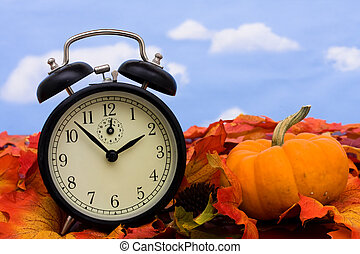 Fall Leaves - Fall coloured leaves with a black clock on a...