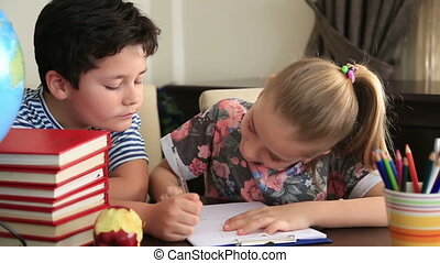 Little boy and girl studying - Elementary students doing...