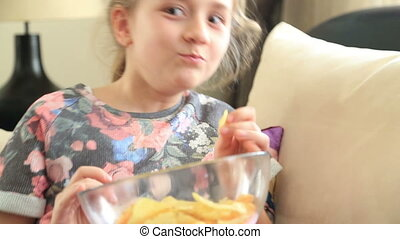 Young girl likes potato chip - Happy little girl eating...
