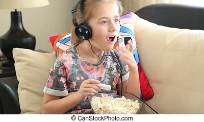 Little girl listening to music and eating popcorn