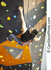 Man practicing rock-climbing on rock wall indoors - Young...