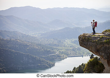 Young mother with baby in sling standing on cliff over river