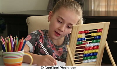 Beautiful schoolgirl doing homework - Little girl study at...