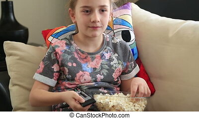 Little girl watching tv - Little girl zapping and eating...
