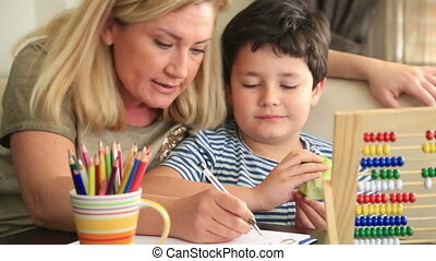 Mother helping her son - Little student doing homework with...