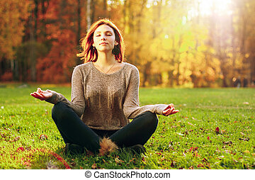 Young attractive female meditate in park. Outdoor shot