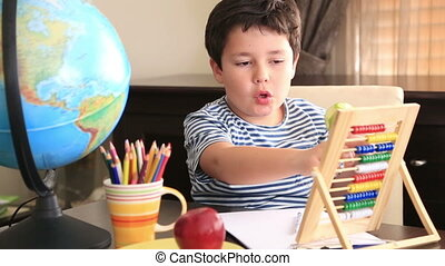 Little student using abacus - Schoolboy writing mathematic...