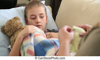 Sick little girl - Sick child lying in bed and coughing