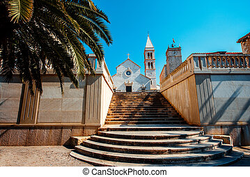 Cathedral in Supetar city with Palm and stairs on foreground...
