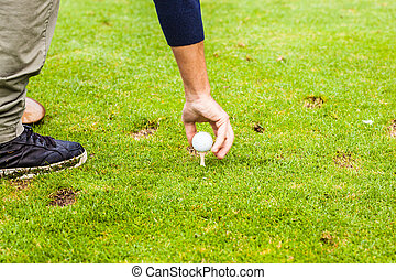 Golf Tee - a golf player planting the tee on the fairway