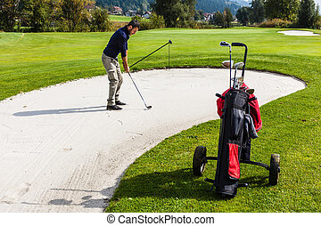 Sand trap hazard - a golf player playing from a sand bunker...