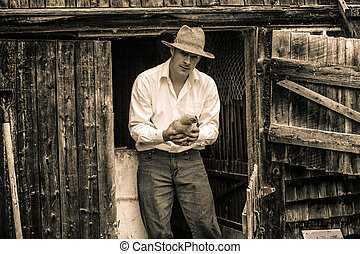 Young Farmer and a Chicken at the Farm