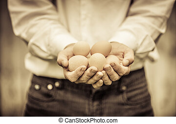 Closeup of Farmer Holding Eggs in front of a Farm