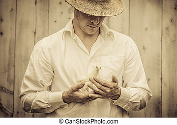 Farmer Holding a Baby Turkey in its hand